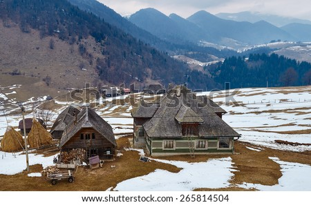 Traditional Romanian household with mountains on background on wintertime - stock photo
