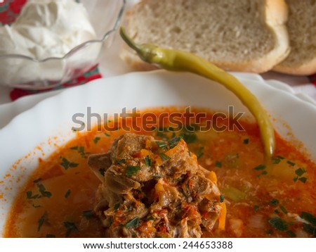 traditional romanian pork bone soup witth sour cream and pickled peppers - stock photo