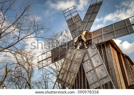 Traditional romanian windmill used by the romanians to grind grains for centuries, against a blue cloudy sky and surrounded by trees - stock photo