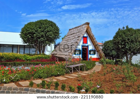 Traditional rural landscape. The village - Museum of the Portuguese island of Madeira. The little white house with a triangular thatched roof and a red door. - stock photo