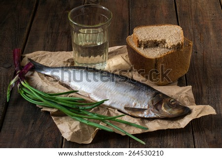 Traditional russian appetizer to vodka: salted herring, green onions and brown bread on paper and wooden table in vintage style - stock photo