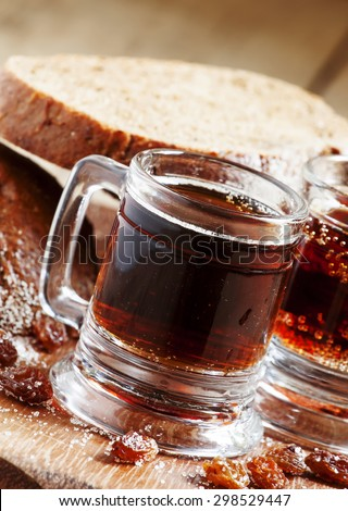 Traditional Russian drink kvass in a mug, with rye bread on a wooden background in rustic style, selective focus