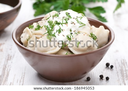 traditional Russian dumplings with sour cream and dill, close-up, horizontal