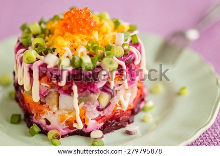 Traditional Russian herring salad, on green plate - stock photo