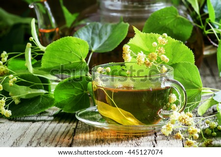 Traditional Russian linden tea, flowers and linden branches, a vintage wooden background, selective focus