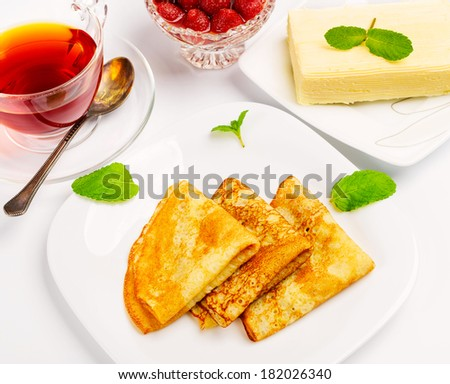 Traditional Russian pancakes with black tea and strawberries. - stock photo