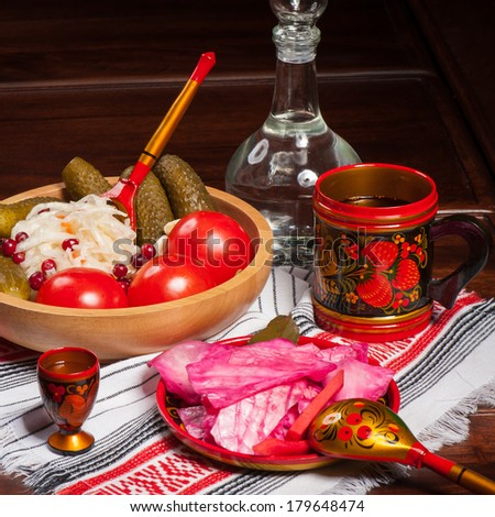 Traditional russian pickled vegetables in painted wooden tableware