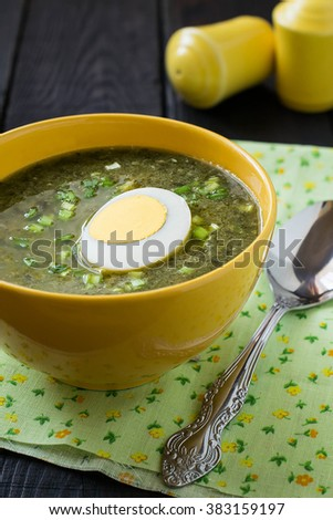 Traditional russian spring sorrel soup with egg in a yellow bowl, plate with rye bread and eggs, spices on a wooden table on wooden table. Selective focus