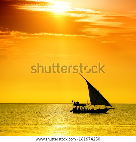 Traditional sailboat on colorful sunset. Lens flare suggestion