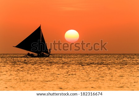 Traditional sailing boat and a tropical sunset - stock photo