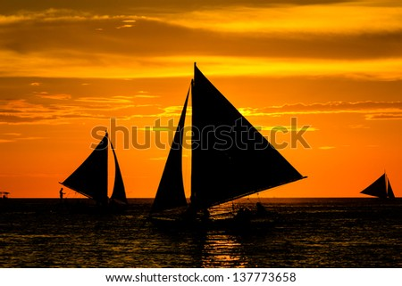 Traditional sailing boats in silhouette in front of a setting sun