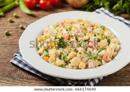 Traditional salad with cooked vegetables with mayonnaise. Wooden background. Front view.