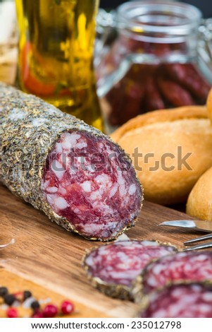 traditional salami with herbs on wooden board and olive oil - stock photo