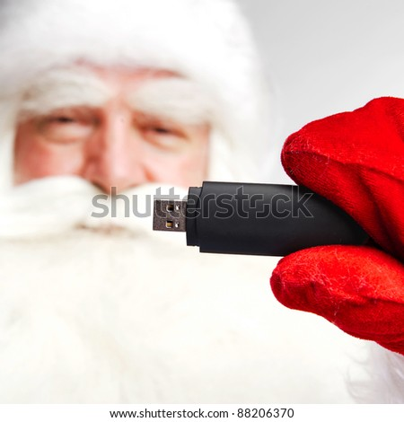 Traditional Santa Claus holding 3g usb modem in his arm on foreground. Isolated on white. - stock photo