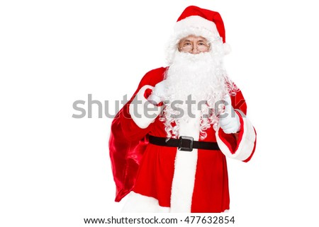Traditional Santa Claus showing his thumb up and carrying sack with presents on white background