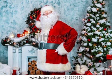 Traditional Santa Claus standing by the fireplace and Christmas tree in a beautiful room, decorated for Christmas. - stock photo