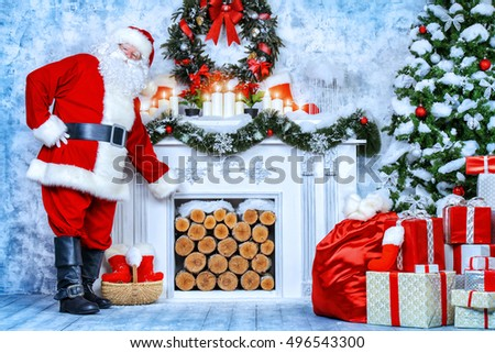 Traditional Santa Claus standing by the fireplace and Christmas tree in a beautiful room, decorated for Christmas.
