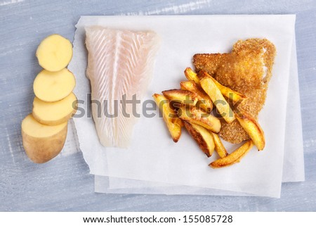 Traditional seafood eating. Raw uncooked fish fillet, fish and chips on wooden background, top view. Delicious healthy fish eating. - stock photo