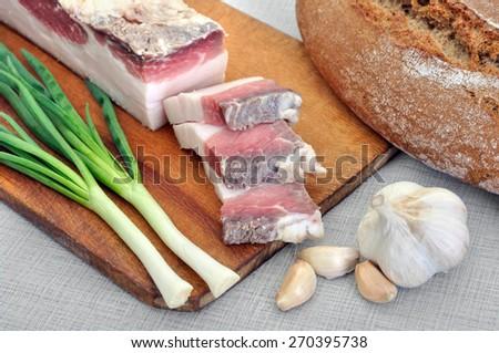 traditional simple ukrainian food: salted fresh lard (salo), garlic, green onion and rye bread - stock photo
