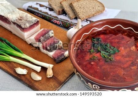traditional simple ukrainian food: ukrainian borscht, salted fresh lard (salo), garlic, green onion and rye bread - stock photo