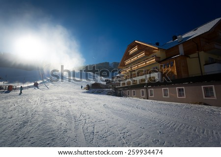 Traditional ski resort at Austrian Alps with working snow cannons at sunny day - stock photo