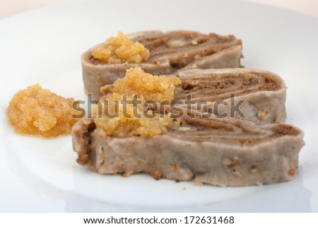 Traditional Slovenian cuisine: Ajdovi struklji - roll cake made with buckwheat flour and filled with walnut and honey filling, cooked in hot water. Usually served with brown butter breadcrumbs - stock photo