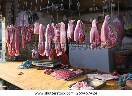 Traditional small Chinese meat store with pork hanging in hooks from the ceiling, and minced meat, knives and scales on counter - stock photo
