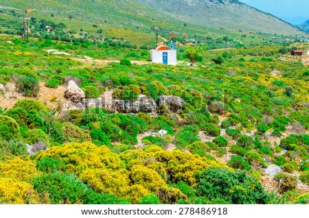 Traditional small Greek church with red roof among bushes, Greece - stock photo
