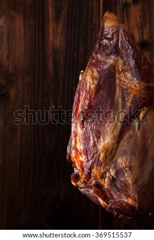 Traditional smoked meat hanging against wooden background. Culinary meat eating.