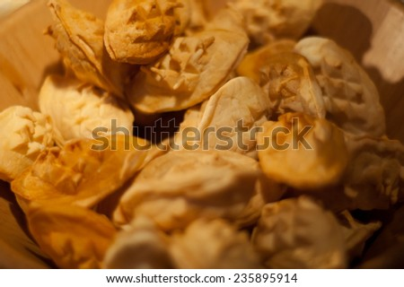 Traditional smoked sheep cheese called oscypek. A lot of small pieces of cheese in a wooden basket. Christmas in Poland, tradition in mountains. Nobody. Macro. - stock photo