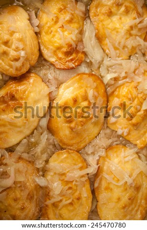 Traditional smoked sheep cheese called oscypek. A lot of small pieces of cheese in a wooden basket with onion. Christmas in Poland, tradition in mountains. Nobody. MAcro. - stock photo