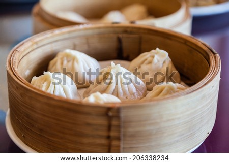 Traditional soup dumpling Xiao Long Bao is a popular Chinese dim sum steamed in bamboo steamers. - stock photo