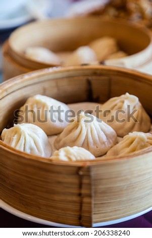 Traditional soup dumpling Xiao Long Bao is a popular Chinese dim sum steamed in bamboo steamers. Vertical Orientation. - stock photo