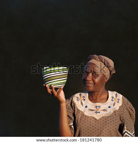Traditional South African Zulu woman basket sales woman on blackboard background - stock photo