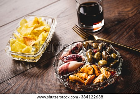 Traditional spanish appetizer with vermouth drink, canned food and chips. - stock photo