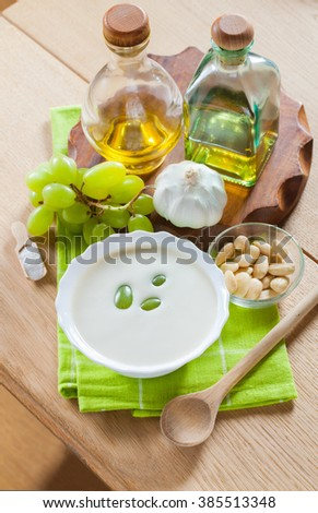 Traditional Spanish dish, cold soup ajoblanco (garlic with almonds, white wine vinegar and olive oil and grapes) in a white bowl with a spoon on a green napkin on a wooden table, vertical - stock photo