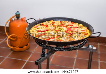 Traditional spanish paella cooking in a pan, with yellow rice and seafood
