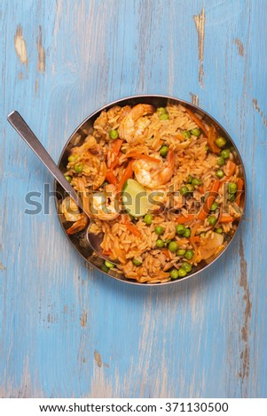 Traditional spanish paella dish with seafood, peas, rice and chicken over grunge blue background. Top view. Selective focus