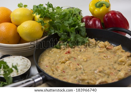 Traditional spicy prawns in frying pan surrounded with herbs, vegetables and fruit - stock photo