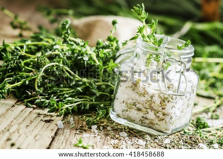 Traditional spicy salt with thyme in a glass jar, vintage wooden background, selective focus - stock photo