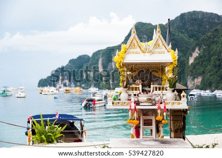 Traditional spirit house in Thailand (san phra phum) against turquoise sea water, ships and mountains.Phi-Phi