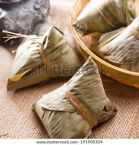 Traditional steamed sticky glutinous rice dumplings. Hot rice dumpling or zongzi. Chinese food dim sum. Asian cuisine. - stock photo