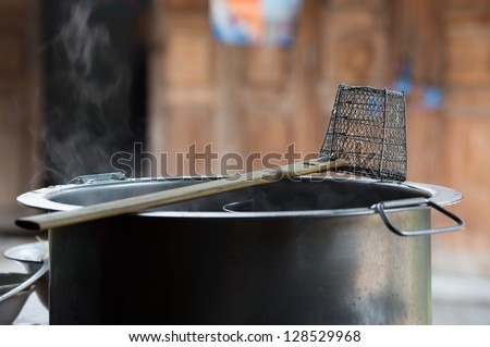 Traditional steel wire mesh noodle strainer on a hot noodle pot - stock photo