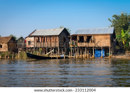 Traditional stilts wooden and bamboo houses and long boats of Intha people in water on Inle lake, Myanmar (Burma)  - stock photo
