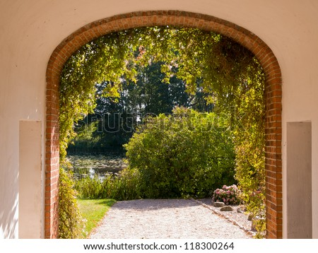 Traditional stone built arch gate leading into a beautiful English garden - stock photo