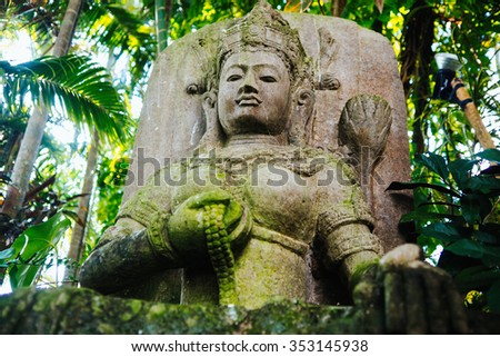 Traditional stone carved statue in the tropical garden
