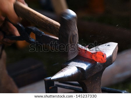 Traditional style blacksmith at work. Hammer hands and iron. - stock photo