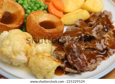 Traditional Sunday roast dinner with Yorkshire puddings and gravy. - stock photo