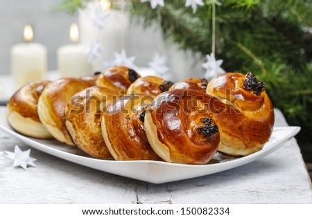 Traditional swedish buns in christmas setting. A saffron bun, in Swedish lussebulle or lussekatt. - stock photo