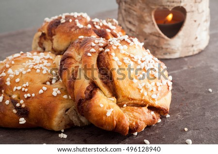 Traditional Swedish cinnamon buns served on a rustic plate. A very popular snack throughout Scandinavia known as Fika when taken with a cup of coffee.